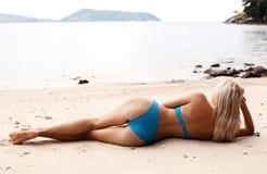 Сексуальная женщина с светлыми волосами в элегантном бикини ослабляя на пляже Стоковая Фотография