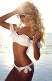 Сексуальная женщина с светлыми волосами в элегантных купальнике и солнечных очках Стоковые Фото