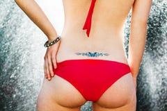 Сексуальная женщина с яркого блеска татуировки задней частью дальше Стоковые Фото
