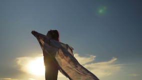 Сексуальная женщина танцуя и держа шарф на пляже на заходе солнца видеоматериал