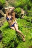Сексуальная красивая девушка в купальнике сидя на камнях среди утесов в джунглях стоковые фотографии rf