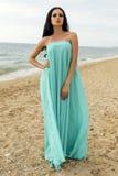 Сексуальная красивая женщина в элегантном платье представляя на пляже Стоковое Изображение