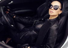 Сексуальная красивая женщина при темные волосы представляя в роскошном автомобиле Стоковое Изображение RF