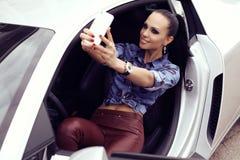 Сексуальная красивая женщина при темные волосы представляя в роскошном автомобиле Стоковая Фотография
