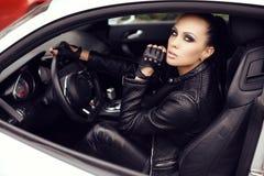 Сексуальная красивая женщина при темные волосы представляя в роскошном автомобиле Стоковые Фото