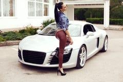 Сексуальная красивая женщина при темные волосы представляя около роскошного автомобиля Стоковое Изображение