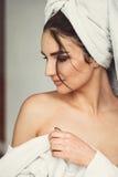 Сексуальная маленькая девочка при темные волосы, большие глаза и темные брови нося белое полотенце whith робы ванны на ее голове Стоковые Изображения