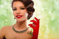 Сексуальная модельная девушка с стеклом шампанского на партии, выпивая шампанском над предпосылкой праздника накаляя Стоковые Изображения RF