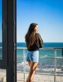 Сексуальная модельная женщина стоит на балконе с морем на предпосылке Стоковое Фото
