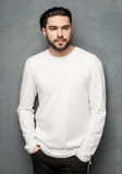 Сексуальная модель человека моды в белых свитере, джинсах и представлять ботинок драматическом стоковые изображения