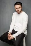 Сексуальная модель человека моды в белых свитере, джинсах и представлять ботинок драматическом стоковое фото rf