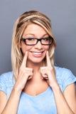 Сексуальная молодая белокурая женщина с поддельной улыбкой для того чтобы показать успех Стоковые Изображения