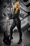 Сексуальная молодая блондинка одела в черной коже с электрической гитарой Стоковое Изображение