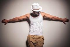Сексуальная молодая вскользь склонность человека на белой стене Стоковые Изображения RF
