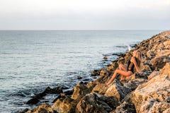 Сексуальная молодая женщина встречает восход солнца на утесах около моря Стоковая Фотография RF
