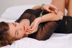 Сексуальная молодая женщина лежит в кровати запертой с Стоковые Изображения