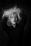 Сексуальная молодая женщина кладя руки в ее disheveled волосы Стоковые Изображения