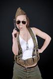 Сексуальная молодая женщина представляя в военной форме WW2 и оружии стоковое фото