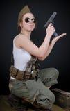 Сексуальная молодая женщина представляя в военной форме WW2 и оружии стоковое изображение