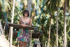 Сексуальная молодая женщина представляя около качания на тропическом пляже, остров Бали рая, Индонезия Солнечный день, счастливые Стоковые Изображения