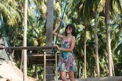 Сексуальная молодая женщина представляя около качания на тропическом пляже, остров Бали рая, Индонезия Солнечный день, счастливые Стоковое Изображение