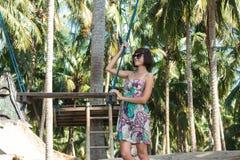 Сексуальная молодая женщина представляя около качания на тропическом пляже, остров Бали рая, Индонезия Солнечный день, счастливые Стоковые Фотографии RF