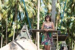 Сексуальная молодая женщина представляя около качания на тропическом пляже, остров Бали рая, Индонезия Солнечный день, счастливые Стоковое Изображение RF