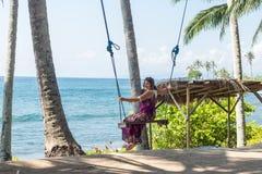 Сексуальная молодая женщина сидя на качании на тропическом пляже, остров Бали рая, Индонезия Солнечный день, счастливые каникулы Стоковое фото RF