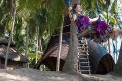 Сексуальная молодая женщина сидя на качании на тропическом пляже, остров Бали рая, Индонезия Солнечный день, счастливые каникулы Стоковое Изображение RF
