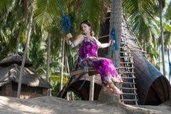 Сексуальная молодая женщина сидя на качании на тропическом пляже, остров Бали рая, Индонезия Солнечный день, счастливые каникулы Стоковые Изображения