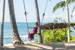 Сексуальная молодая женщина сидя на качании на тропическом пляже, остров Бали рая, Индонезия Солнечный день, счастливые каникулы Стоковая Фотография RF