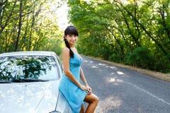 Сексуальная молодая женщина стоя на дороге около автомобиля Стоковая Фотография