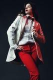 Сексуальная представляя женщина в белом пальто и красных брюках Стоковые Фотографии RF