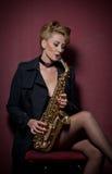 Сексуальная привлекательная женщина при саксофон представляя на красной предпосылке Молодой чувственный белокурый играя саксофон  Стоковая Фотография RF