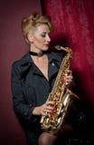 Сексуальная привлекательная женщина при саксофон представляя на красной предпосылке Молодой чувственный белокурый играя саксофон  Стоковое Изображение