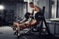 Сексуальная разминка девушки фитнеса с штангой в спортзале, женщина и человек в спорте носят с совершенным мышечным телом Стоковые Фотографии RF