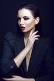 Сексуальная строгая женщина с составом и модным стилем причёсок представляет в студии на черной предпосылке Стоковые Фото