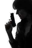 Сексуальная сыщицкая женщина держа направлять силуэт оружия стоковое фото rf