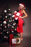 Сексуальное белокурое Санта в красном платье с настоящими моментами около рождественской елки Стоковые Фото
