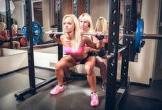 Сексуальные женщины в спортзале делая сидение на корточках с штангой Стоковая Фотография RF