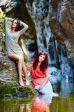Сексуальные женщины сидя на утесе горы Стоковое Фото