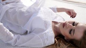 Сексуальный модельный отдыхать на бунгале, солнце испускает лучи в белом занавесе, видеоматериал