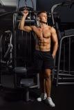 Сексуальный, мышечный молодой человек стоя в шортах против спортзала, полной диаграммы тела стоковое фото