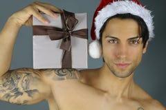 Сексуальный Санта Клаус - человек держа подарок на рождество Стоковые Изображения RF