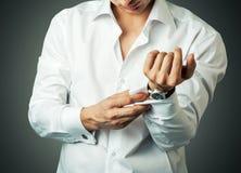 Сексуальный человек застегивает запонку для манжет на французских тумаках Стоковые Фото
