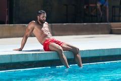 Сексуальный человек отдыхая на бассейне стоковое фото rf