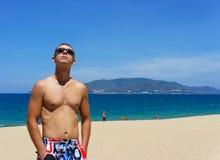 Сексуальный человек представляя на пляже Стоковые Фото