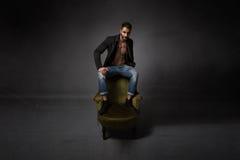 Сексуальный человек сидя на зеленой софе стоковое фото