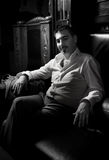 Сексуальный человек сидя на кожаном стуле Стоковая Фотография RF