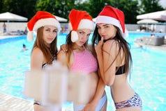 3 сексуальных девушки в бикини и красных крышках рождества Стоковое Фото